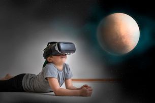 Young boy lying on floor, wearing virtual reality headset, looking at planet, digital compositeの写真素材 [FYI03574309]