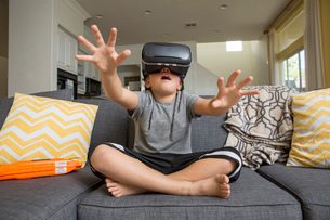 Young boy sitting cross legged on sofa, wearing virtual reality headset, hands reaching out in frontの写真素材 [FYI03574310]