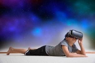 Young boy lying on floor, wearing virtual reality headset, looking into night sky, digital compositeの写真素材 [FYI03574312]