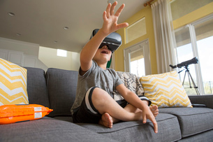 Young boy sitting cross legged on sofa, wearing virtual reality headset, hands reaching out in frontの写真素材 [FYI03574313]