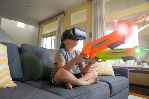 Young boy sitting cross legged on sofa, wearing virtual reality headset, holding laser guns, digitalの写真素材 [FYI03574314]