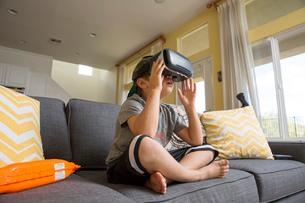 Young boy sitting cross legged on sofa, wearing virtual reality headsetの写真素材 [FYI03574315]