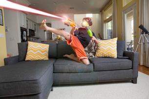 Young boy on sofa, wearing virtual reality headset, kicking leg, firing laser guns, digital compositの写真素材 [FYI03574316]
