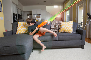 Young boy on sofa, wearing virtual reality headset, firing laser guns, digital compositeの写真素材 [FYI03574317]