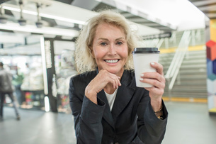 Portrait of mature woman with takeaway coffee in shopping mall cafeの写真素材 [FYI03574384]