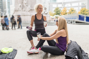 Two mature female friends training in city, chatting with takeaway coffeeの写真素材 [FYI03574395]