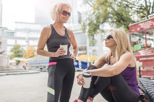Two mature female friends training in city, chatting with takeaway coffeeの写真素材 [FYI03574396]