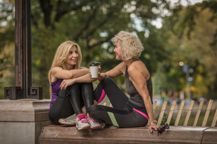 Two mature female friends training in park, sitting on wall with takeaway coffeeの写真素材 [FYI03574397]