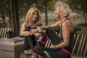 Two mature female friends training in park, sitting on wall with takeaway coffeeの写真素材 [FYI03574398]