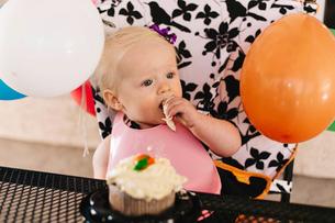 Baby girl sitting in high chair, eating birthday cakeの写真素材 [FYI03574427]