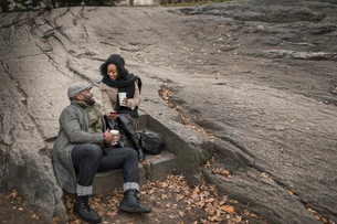 Couple sitting on step in park with takeaway coffeeの写真素材 [FYI03574442]
