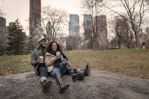 Couple sitting on rock in park with takeaway coffeeの写真素材 [FYI03574443]