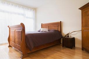 Antique wooden queen size sleigh bed in master bedroom of renovated ground floor apartment in old reの写真素材 [FYI03574464]