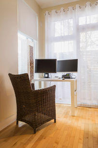 High-back wicker chair and table with desk top computer in home office of master bedroom in renovateの写真素材 [FYI03574465]