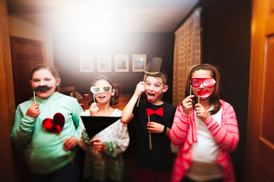 Portrait of boy and three girls holding sunglasses and mustache stick masks at partyの写真素材 [FYI03574481]