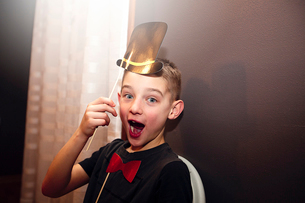 Portrait of boy holding bow tie and top hat stick masks posing at partyの写真素材 [FYI03574482]