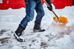 Man shovelling snow from pathway, low sectionの写真素材 [FYI03574541]