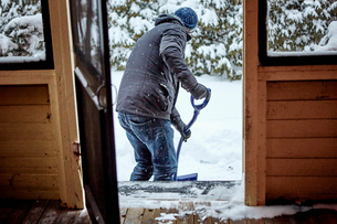 Man shovelling snow from pathway, rear viewの写真素材 [FYI03574542]