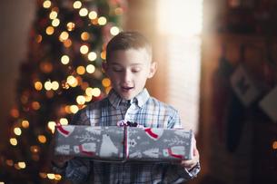 Young boy holding christmas giftの写真素材 [FYI03574547]