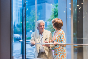 Senior couple using hotel revolving doorの写真素材 [FYI03574609]
