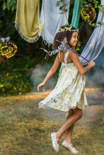 Young girl dressed as fairy, holding wand, playing outdoorsの写真素材 [FYI03574640]