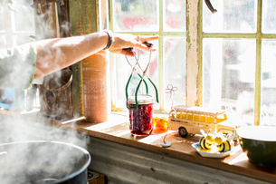 Woman using tongs to remove beetroot preserves jar from steaming saucepanの写真素材 [FYI03574722]