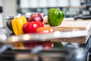 Still life of fresh peppers and red onion on chopping board in kitchen, close-upの写真素材 [FYI03574801]