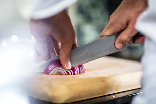 Chef slicing red onion, close-upの写真素材 [FYI03574811]