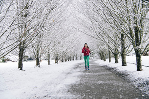 Woman jogging along pathway, in snow covered rural settingの写真素材 [FYI03574818]