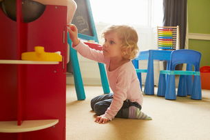 Female toddler playing on playroom floorの写真素材 [FYI03574891]