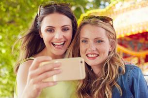 Women taking selfie, carousel in background, London, UKの写真素材 [FYI03574962]