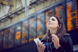 Woman looking at departure information, London, UKの写真素材 [FYI03574967]