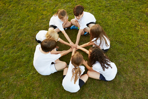 Overhead view of boy and girl sport team sitting on grass in circle on playing fieldの写真素材 [FYI03575063]