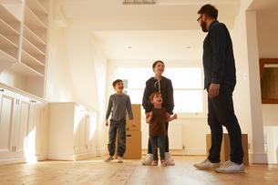 Mid adult man organising three children in new homeの写真素材 [FYI03575115]
