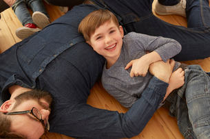 Overhead portrait of boy and father playing on floorの写真素材 [FYI03575124]