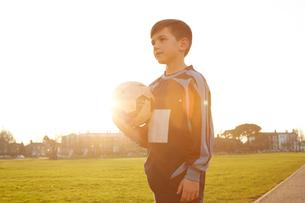 Boy football player holding ball in sunlit parkの写真素材 [FYI03575133]