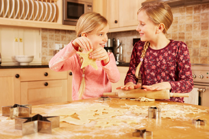 Two girls baking star shape pastry at kitchen tableの写真素材 [FYI03575142]