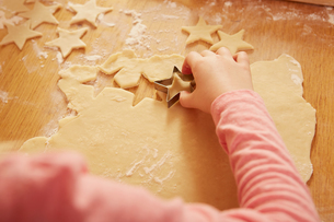 Over shoulder cropped view of girl making star shape pastry at kitchen tableの写真素材 [FYI03575143]