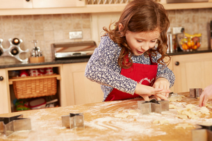 Girl baking star shape pastry at kitchen tableの写真素材 [FYI03575144]