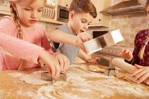 Girls and boy baking star shape pastry at kitchen tableの写真素材 [FYI03575145]
