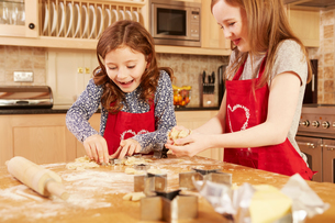 Two girls making star shape pastry at kitchen tableの写真素材 [FYI03575146]