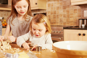 Female toddler and big sister making star shape pastry at kitchen tableの写真素材 [FYI03575147]
