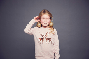 Portrait of young girl wearing Christmas jumper and bauble earringsの写真素材 [FYI03575172]
