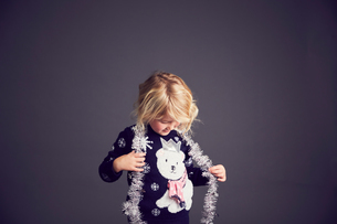 Young girl wearing Christmas jumper and tinsel around neckの写真素材 [FYI03575174]