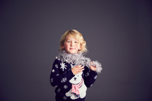 Portrait of young girl wearing Christmas jumper and tinsel around neckの写真素材 [FYI03575176]
