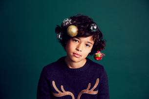 Portrait of teenage boy wearing Christmas jumper, and baubles in hairの写真素材 [FYI03575179]