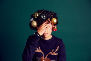 Teenage boy wearing Christmas jumper, and baubles in hair, covering face with handの写真素材 [FYI03575180]