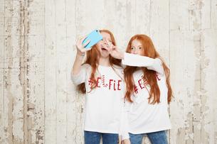 Portrait of twin sisters wearing Christmas jumpers, taking selfie using smartphoneの写真素材 [FYI03575183]