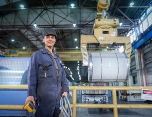 Female apprentice electrician in car factory, portraitの写真素材 [FYI03575202]
