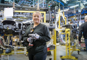 Female apprentice engineer on production line in car factory, portraitの写真素材 [FYI03575224]